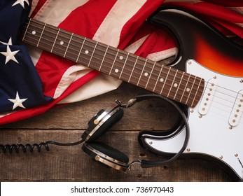Old used rock guitar with headphones and the American flag on rustic wood, music or sound concept background