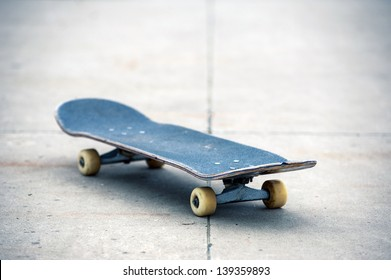 Old used skateboard isolated on the ground. Shallow depth of field.
