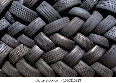 Old used tires stacked with herringbone pattern, taken outdoors in the sunshine