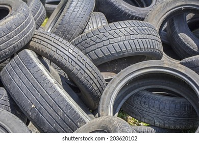 Old used tires stacked on the grass