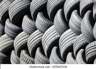 Old used tires that are lined up in a pile.