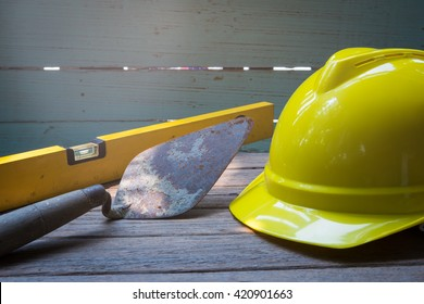 Old used trowel for masonry tools and yellow hard hat of worker