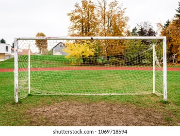 Old vacant football soccer goal gate in rural grass field. Old sports field with rusty goal and net on meadow with muddy front line.