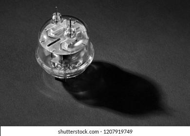 Old vacuum tube on black background. Black and white.