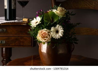 Old vase of ceramic on a chair with flowers and botlle and glass of wine in the background