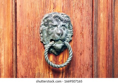 Old Venetian metal Veneto lion head door knocker on the wooden door of old Venice palace