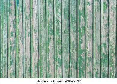 Old vertical boards with remains of green paint as background
