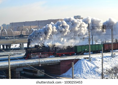 The old, very beautiful steam locomotive rides with a lot of smoke from the pipe through the sleeping area of the city. St. Petersburg