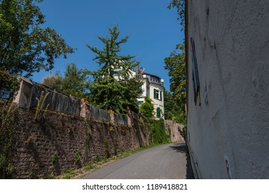 Old vibrant narrow street on a hillside with stone fence