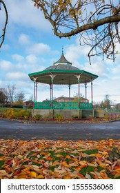 An old victorian bandstand in a park surrounded by benches and fallen autumn leaves