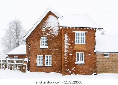 Old Victorian house with roof and brick walls covered in snow in winter