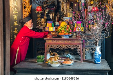 Old Vietnamese man preparing altar with foods for the last meal of year. The penultimate New Years Eve - Tat Nien, the meal finishing the entire year. Vietnam lunar new year.