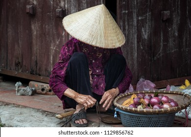 Old Vietnamese woman sells vegetables in the street of ancient town Duong lam,Vietnam