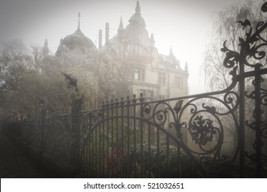 Old villa with iron fence in morning fog