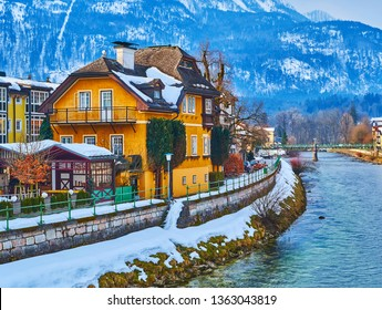 The old villa on the snowbound  bank of Traun river with a slope of Mount Katrin on background, Bad Ischl, Salzkammergut, Austria.