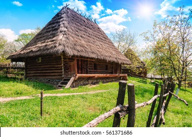 old village house with straw roof in summer