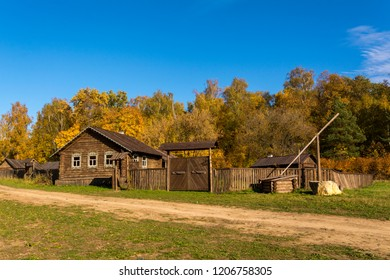Old village in Russia in autumn. House with wooden fence and well.
