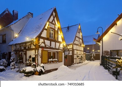 An old village street with half-timbered houses and christmas lights at night during snowfall in Lachen, Neustadt an der Weinstrasse, Germany.