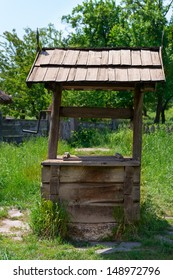 Old village well with a wood roof with green garden on background