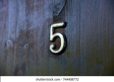 Old vintage aged scratched number 5 five letter on the old door