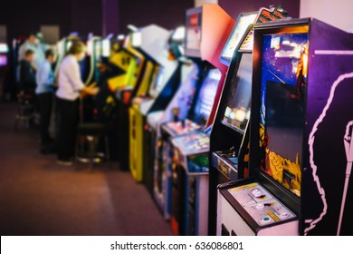 Old Vintage Arcade Games in a dark room and players playing video games in the background