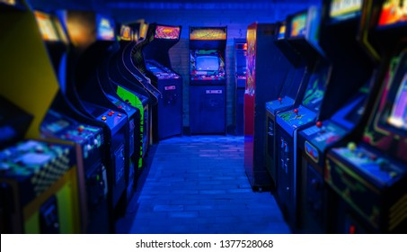 Old Vintage Arcade Video Games in an empty dark gaming room with blue light with glowing displays and beautiful retro design on a wide landscape photo