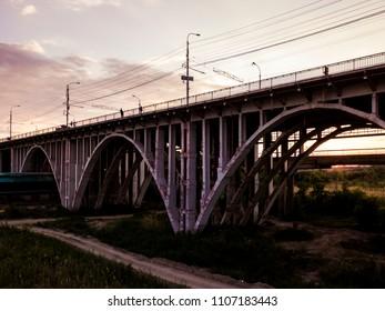 old vintage arch bridge against the sunset sky
