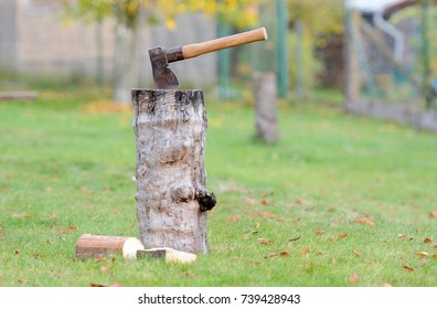 Old vintage axe is stuck in a piece of log wood used for chopping other wood.