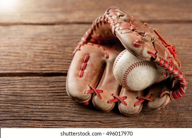 old vintage baseball glove with the baseball held in the palm on wooden background (Shallow depth of field)