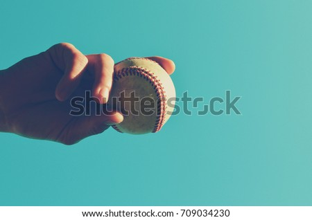 Old vintage baseball held by pitcher horizontal toward sky. Baseball game background image.