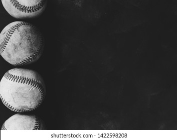 Old vintage baseballs in line for sports border with copy space.  Black and white baseball background for ball player concept.