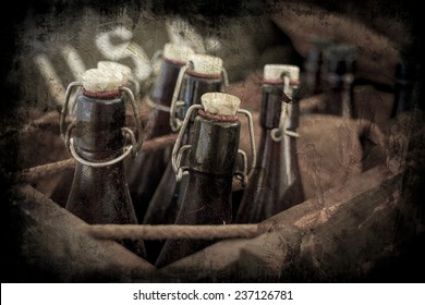Old vintage beer bottles in a wooden crate with a grunge effect.