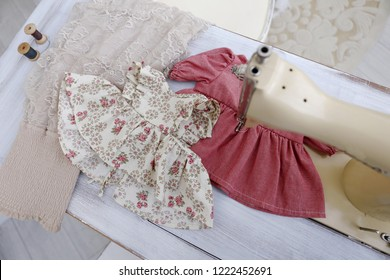 old vintage beige sewing machine and red little dress for girl and doll in atelier with white brick walls