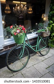 An old vintage bike displaying baskets of flowers outside an antique shop in Britain.