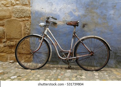 Old vintage bike in the street, against blue wall