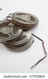 Old vintage bobbins with magnetic tapes on a white background