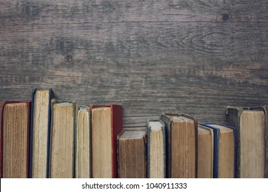 Old vintage book spines in a row with copy space over rustic dark wood table background texture