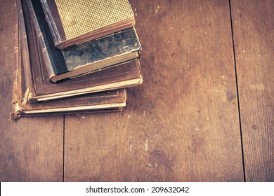 Old vintage books on wooden desk. Retro style filtered photo