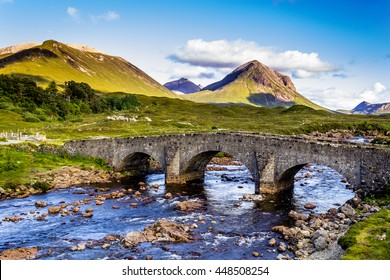 Old vintage brick bridge crossing river in  Sligachan, Isle of Skye, Scotland with blue sky, hills and mountains in the background