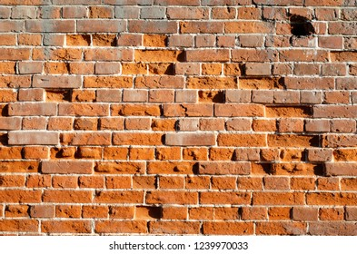Old Vintage brick wall for background. Distressed Wall With Broken Bricks Texture in direct sunlight.