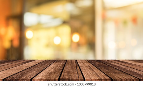 old vintage brown wood tabletop with blurred restaurant bar cafe light color background for promote and advertise product on display