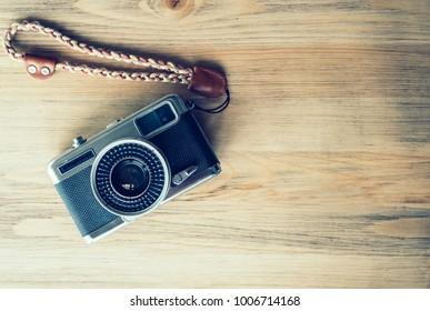 Old vintage camera on wooden background.