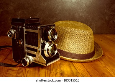 Old vintage camera with photographer fedora hat