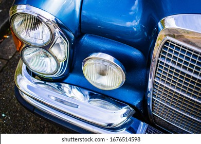 Old vintage car in blue with grille and lamps with lots of chrome