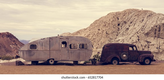 Old vintage caravan and truck abandoned in the desert