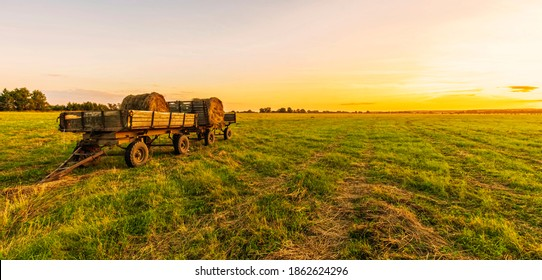 Old vintage carriage with hay stacks in green shiny field with beautiful sunset , hay cart in country valley during sunrise , wagon with haystacks and scenic view