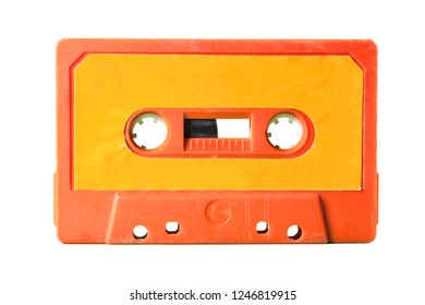 An old vintage cassette tape from the 1980s (obsolete music technology). Vivid colors: coral red plastic body, orange paper label, isolated on white.