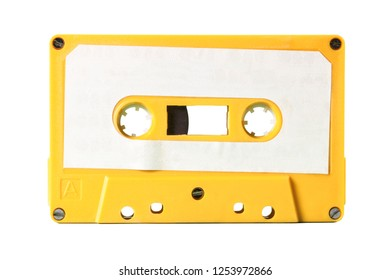 An old vintage cassette tape from the 1980s (obsolete music technology). Electro yellow plastic body, white paper label, isolated.