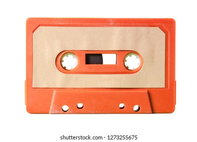 An old vintage cassette tape from the 1980s (obsolete music technology). Vivid colors: dark orange plastic body, sand pale pink label.