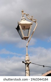 Old Vintage Cast Iron Lantern on Post against Cloudy Blue Sky